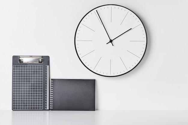 Fournitures de bureau, horloge collante et ronde sur blanc