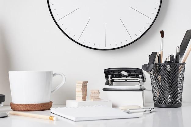 Fournitures de bureau et horloge murale sur blanc