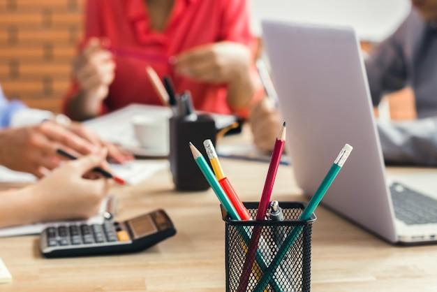 Fournitures de bureau avec ordinateur portable sur la table de réunion avec des gens d'affaires flou en arrière-plan