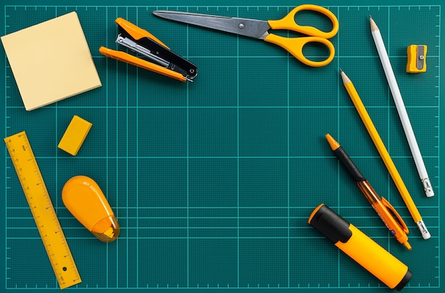 Fournitures de bureau de papeterie orange sur le tapis de coupe vert, plat lay picture