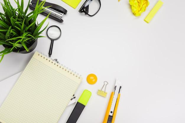 Fournitures de bureau avec plante et verres