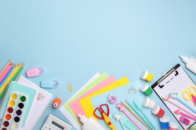 Fournitures de bureau à plat. divers papeterie sur fond bleu clair. retour à l'école. un cadre fait d'accessoires scolaires.