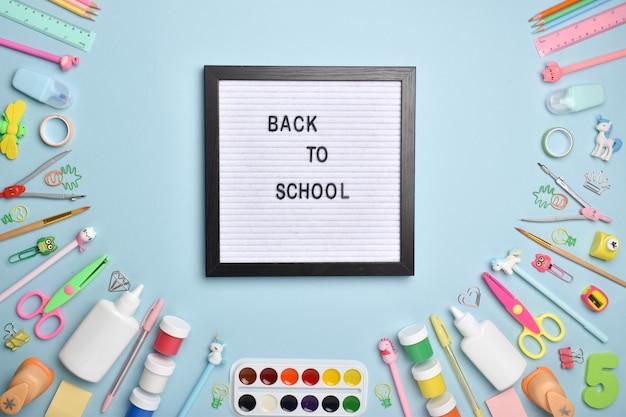 Fournitures de bureau à plat. retour à l'école. diverses fournitures de bureau sur fond bleu clair avec une planche en feutre. disposition plate, vue de dessus, un endroit pour copier.