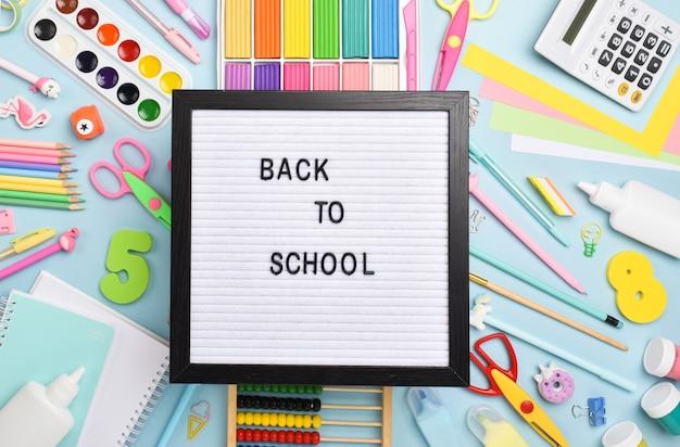 Fournitures de bureau à plat. retour à l'école. diverses fournitures de bureau sur fond bleu clair avec une planche en feutre.