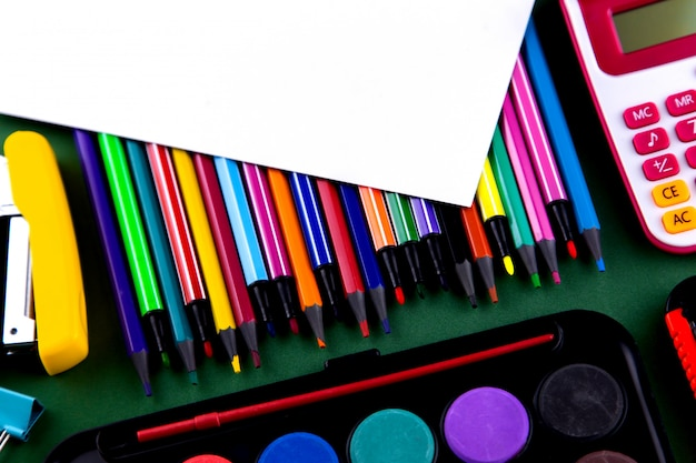 Fournitures de bureau scolaire sur un bureau de fond vert avec du papier blanc au-dessus de l'espace de copie. retour au concept d'école.