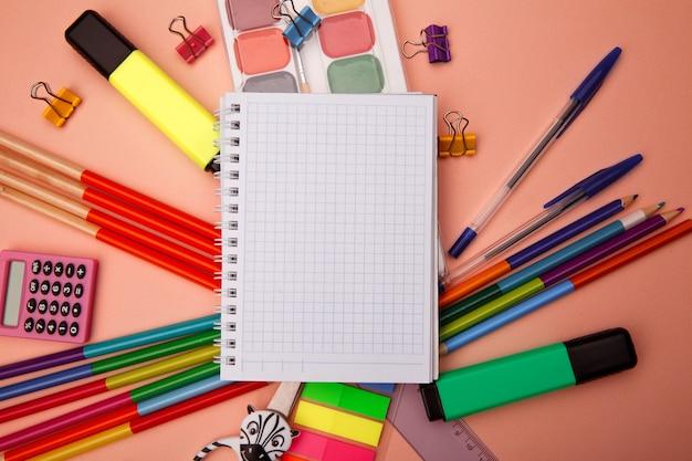 Fournitures de bureau scolaire sur fond rose