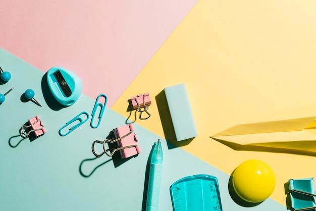 Fournitures de bureau et scolaires essentielles sur fond multicolore