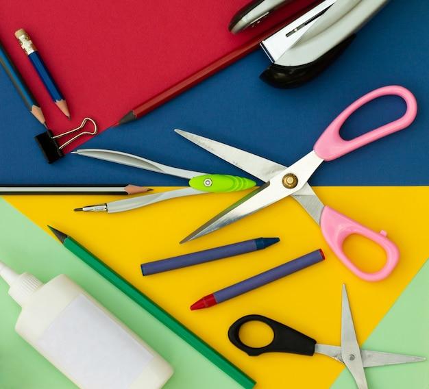 Fournitures de bureau ou scolaires sur fond coloré. vue de dessus.