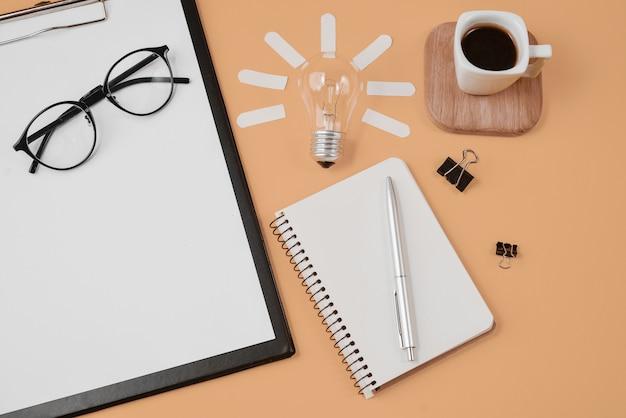 Fournitures de bureau de style bureau avec stylo, bloc-notes, lunettes, tasse à café et ampoule