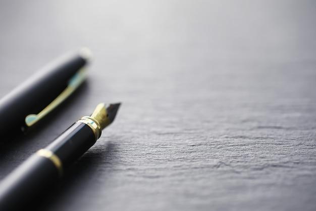 Fournitures de bureau sur la table. un stylo. stylo d'affaires au bureau sur une surface en pierre.