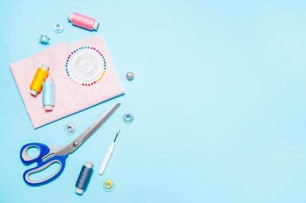 Fournitures de couture, patron et accessoires pour travaux d'aiguille sur fond bleu, coutures, broderies. espace pour le texte. lay plat, vue de dessus.