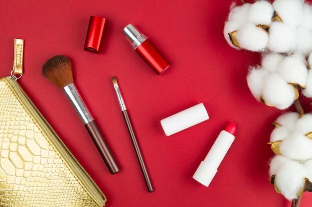 Fournitures de maquillage pour femmes sur la table. coton, pinceaux et rouge à lèvres