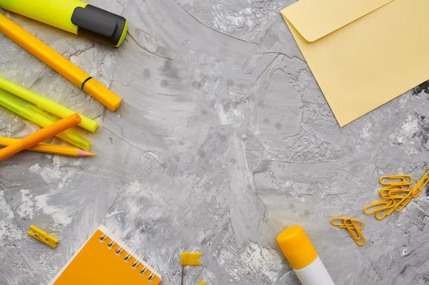 Fournitures de papeterie de bureau en gros plan de tons jaunes, fond de marbre. accessoires scolaires ou éducatifs, outils d'écriture et de dessin, crayons et caoutchoucs, règle et trombones