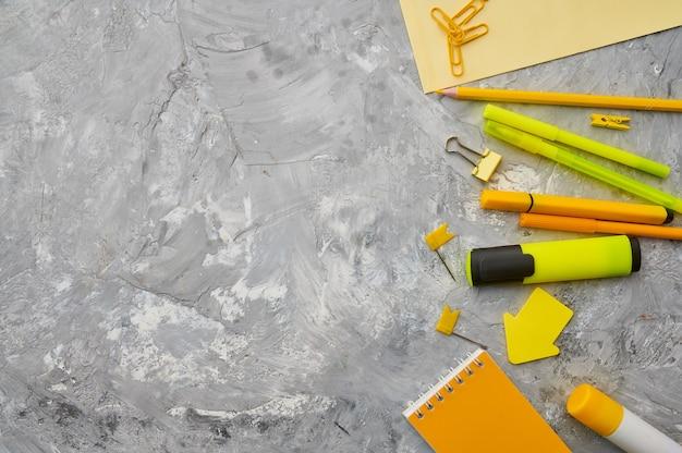 Fournitures de papeterie de bureau en gros plan de tons jaunes, mur de marbre. accessoires scolaires ou éducatifs, outils d'écriture et de dessin, crayons et caoutchoucs, etc.