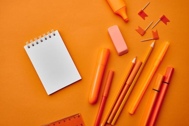 Fournitures de papeterie de bureau, vue macro, mur orange. accessoires scolaires ou éducatifs, outils d'écriture et de dessin