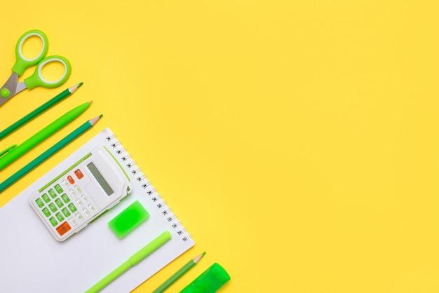 Fournitures de papeterie scolaire sur table jaune avec un espace de copie.