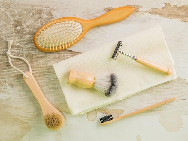 Fournitures de rasage, brosse à dents et peignes sur une serviette sur une table en bois. hygiène. mise à plat.