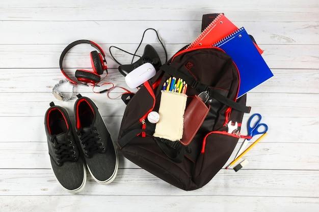 Fournitures de sac à dos scolaire et tablette avec écouteurs.
