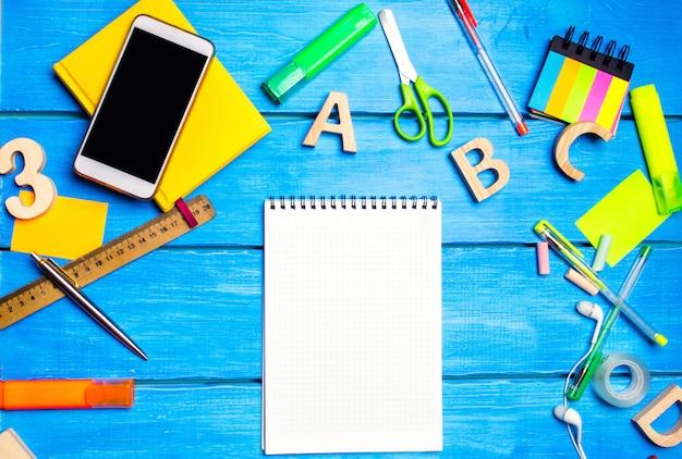 Fournitures scolaires sur le banc d'école, papeterie, concept d'école, fond bleu, chaos créatif