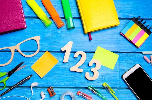 Fournitures scolaires sur le banc d'école, papeterie, concept d'école, fond bleu