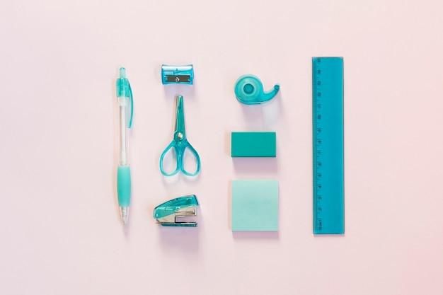 Fournitures scolaires bleues sur une surface rose clair