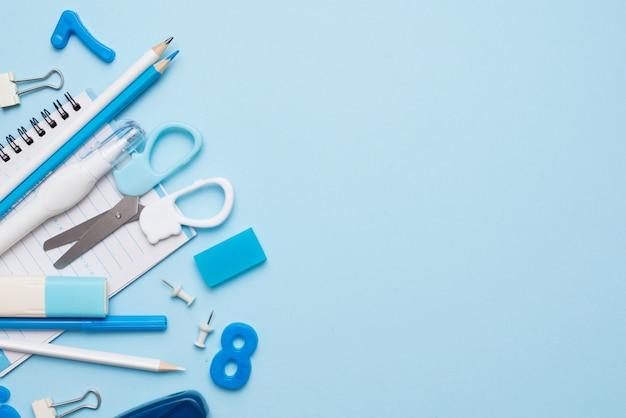 Fournitures scolaires bleues sur table bleue