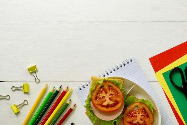 Fournitures scolaires et boîte à lunch avec des sandwichs à la saucisse sur un fond en bois blanc