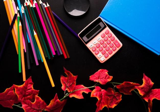 Fournitures scolaires et branche de lierre rouge dispersés sur fond noir