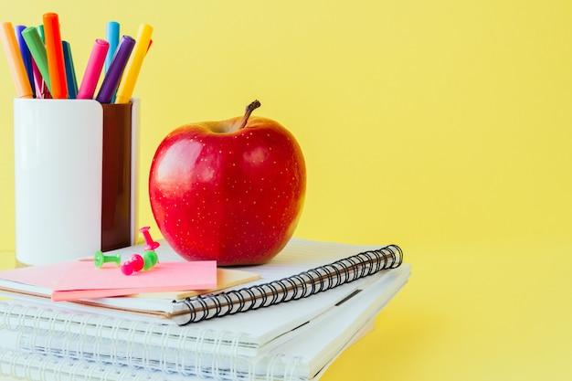 Fournitures scolaires et de bureau sur la table de la classe sur jaune