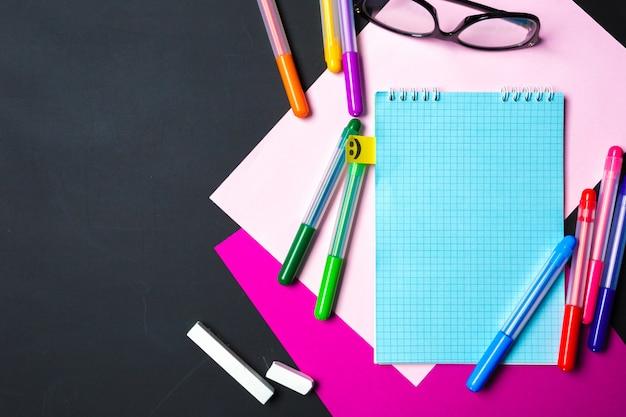 Fournitures scolaires et de bureau sur tableau noir, vue de dessus plat poser
