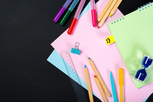 Fournitures scolaires et de bureau sur tableau noir