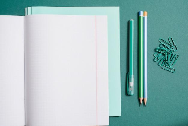 Fournitures scolaires, cahier, stylo et crayon sur fond vert.