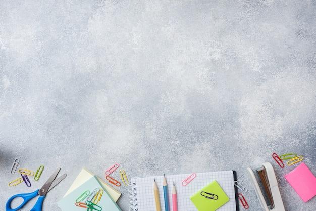 Fournitures scolaires, cahiers de crayons sur fond gris avec espace de copie.