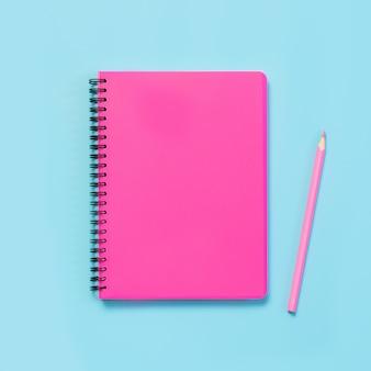 Fournitures scolaires, cahiers et stylos roses sur bleu vif. vue de dessus, plat poser. espace de copie.