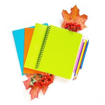 Fournitures scolaires colorées, cahiers et réveil sur blanc.