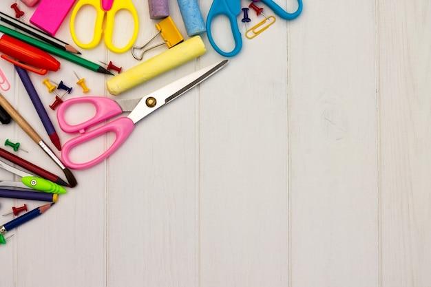 Fournitures scolaires colorées sur un fond en bois blanc, . vue de dessus. espace de copie. concept d'éducation et de retour à l'école.