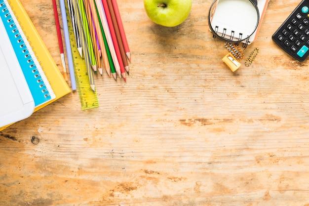 Fournitures scolaires colorées sur fond en bois