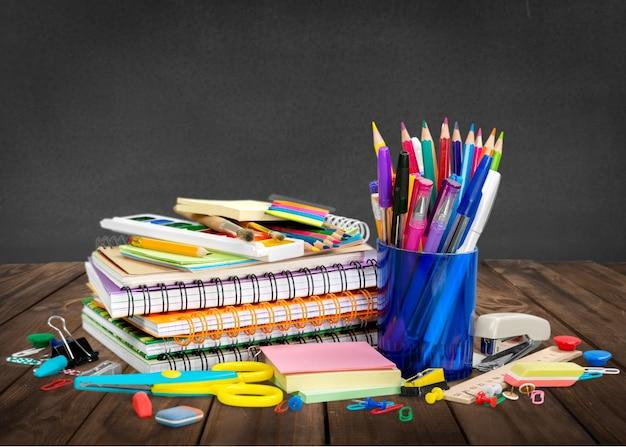 Fournitures scolaires colorées sur fond de tableau noir