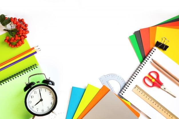 Fournitures scolaires colorées, livre et réveil sur blanc.