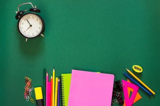 Fournitures scolaires colorées, livre et réveil sur le vert.