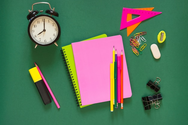 Fournitures scolaires colorées, livre rose et réveil sur vert.