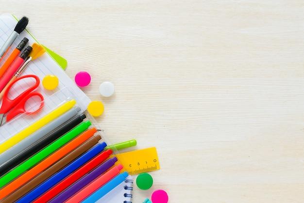 Fournitures scolaires colorées lumineuses pour l'école ou l'université sur le fond en bois blanc retour à l'école