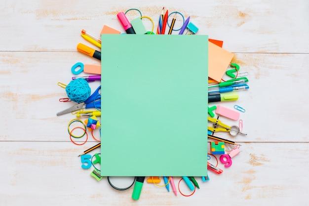 Fournitures scolaires colorées et papier vert.
