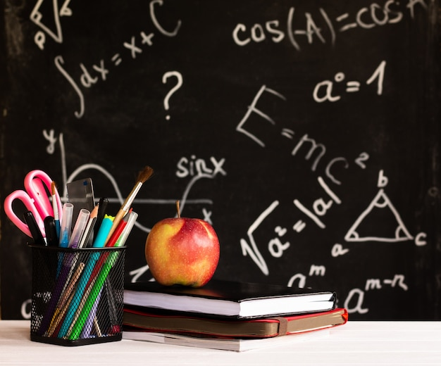 Fournitures scolaires colorées, pomme, livres sur un comptoir blanc sur fond de tableau avec des formules. notion d'éducation