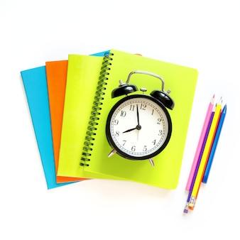 Fournitures scolaires colorées et réveil sur blanc.