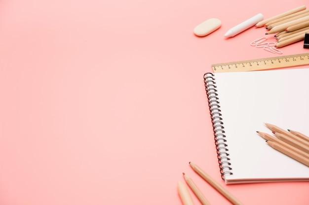 Fournitures scolaires colorées sur rose pastel. vue de dessus, plat poser. fond