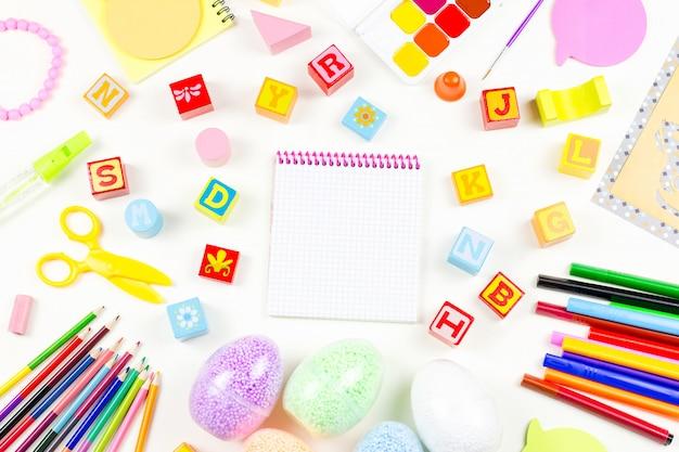 Fournitures scolaires, concept de créativité enfant à plat. divers outils artistiques pour enfants sur bureau blanc. espace copie