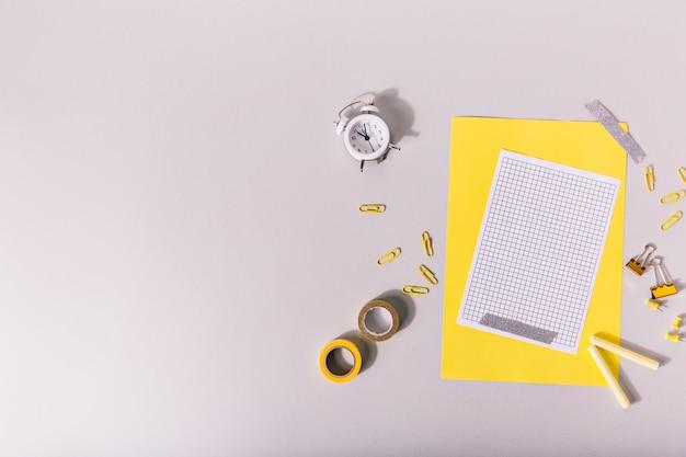 Fournitures scolaires de couleur jaune disposées de manière créative sur le bureau