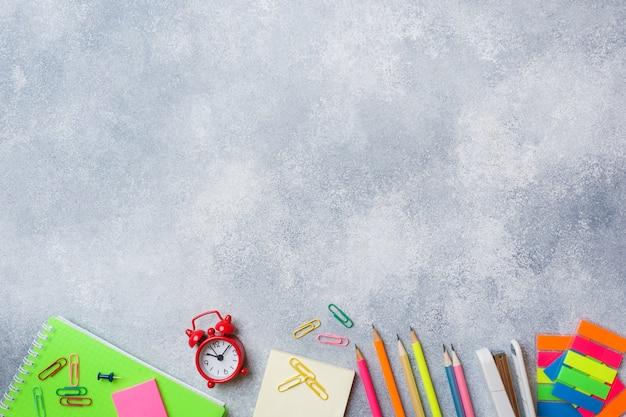 Fournitures scolaires, crayons cahiers sur fond gris avec espace de copie.