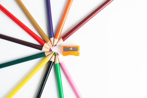 Fournitures scolaires et crayons de couleur sur blanc